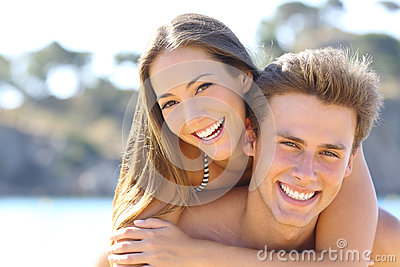 couple-perfect-smile-posing-beach-happy-white-teeth-looking-camera-58754704